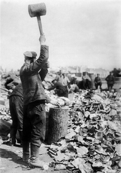 WW1. Soldier smashing used tins with a hammer The tins will be returned to Germany for recycling undated probably in 1915/1916