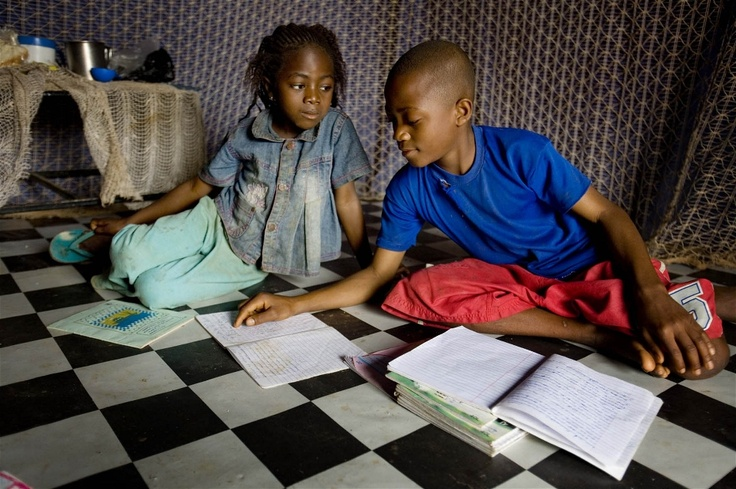 Helen does her homework with her brother Jacob in Kaduna State, Nigeria. Both have just taken their dose of Mectizan to prevent them from contracting river blindness