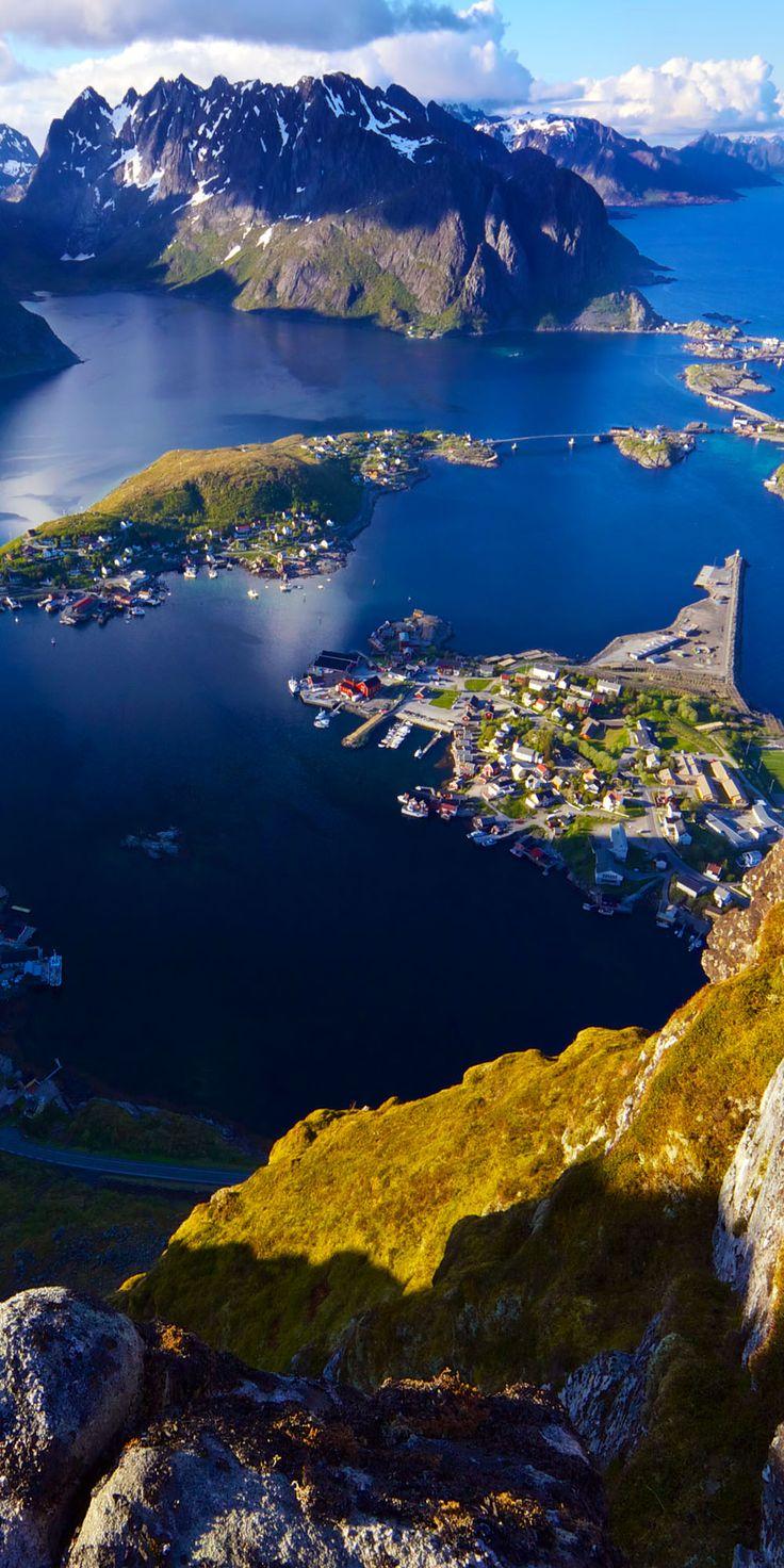 A vista cênica das ilhas Lofoten na parte superior da montanha Reinebringen, com pitoresca cidade de Reine e os fiordes vizinhos. Noruega.  Fotografia: Harvepino | via Shutterstock.