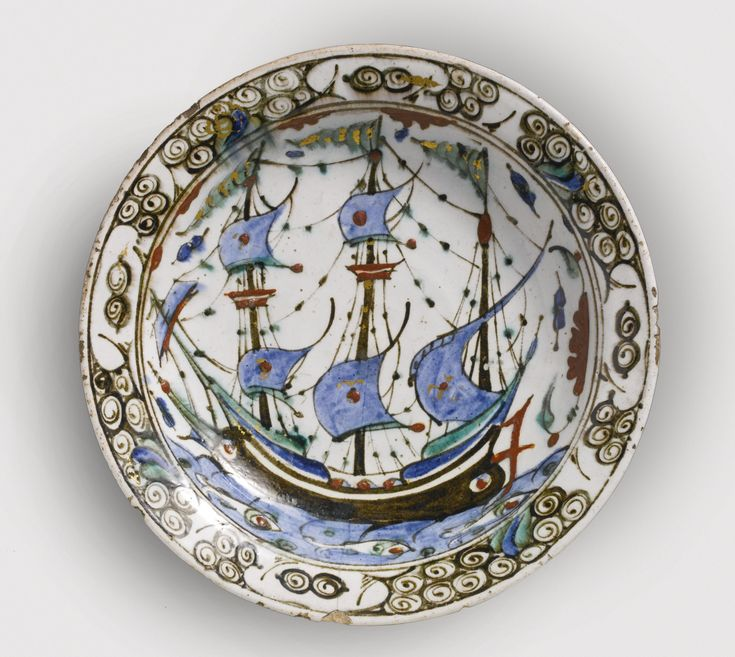An Ottoman Polychrome Pottery Dish, Iznik, circa 2nd quarter of the 17th Century with low pierced foot-ring, the interior painted in blue, black, green, and red on a white ground with a three-masted galleon at sea in a strong wind, pennants flying above, three fish swimming below, six small florets on the exterior; traces of gilding. Diameter 11 5/8 in. 29.5 cm.