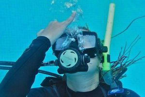 A scuba diver signals that she is ready to begin the open water mask clearing skill. Mask clearing is an important open water skill.: Step 5: Repeat