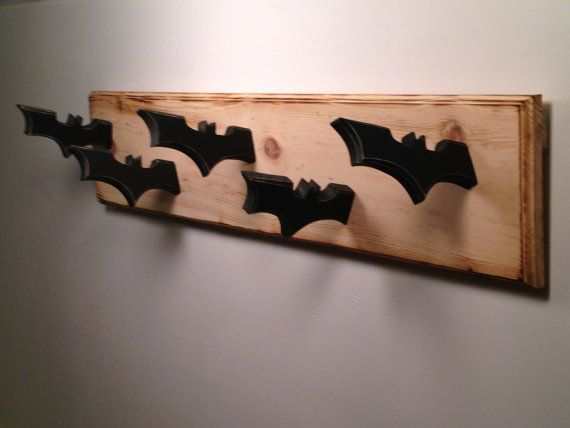 "Hang up your cape and cowl with this handcrafted, batman inspired coat rack. The black ""batarangs"" are crafted out of wood, and feature beveled and"
