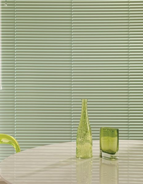 Green Venetian blinds are both stylish and practical.