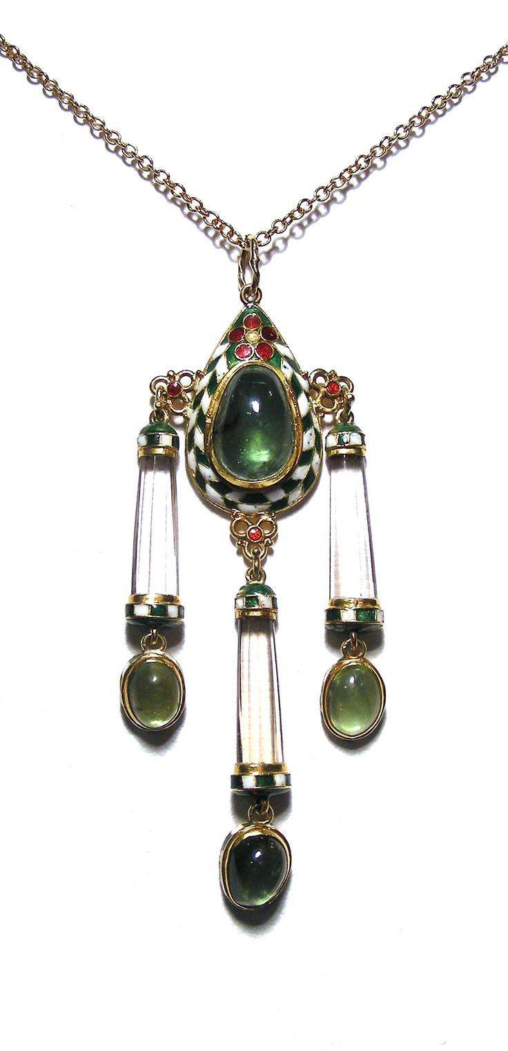 An Arts and Crafts Enamel and Gem-set Pendant by Henry Wilson in the form of a pear shaped green tourmaline cabochon, surrounded by a border of chequered green and white enamel topped by a stylised red enamel flower, from which are suspended three carved rock crystal  rods with enamel detailing and three green tourmaline cabochons.  English, circa 1900| JV