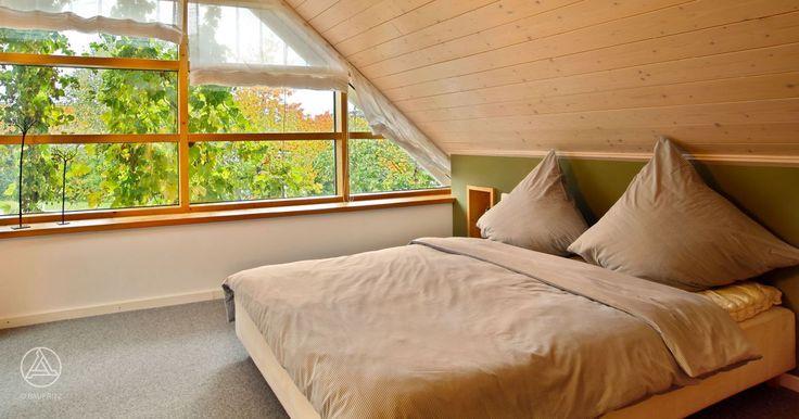 Elternschlafzimmer mit Ankleide und großzügiger Giebelverglasung – Baufritz Schwedenhaus Edition Rot