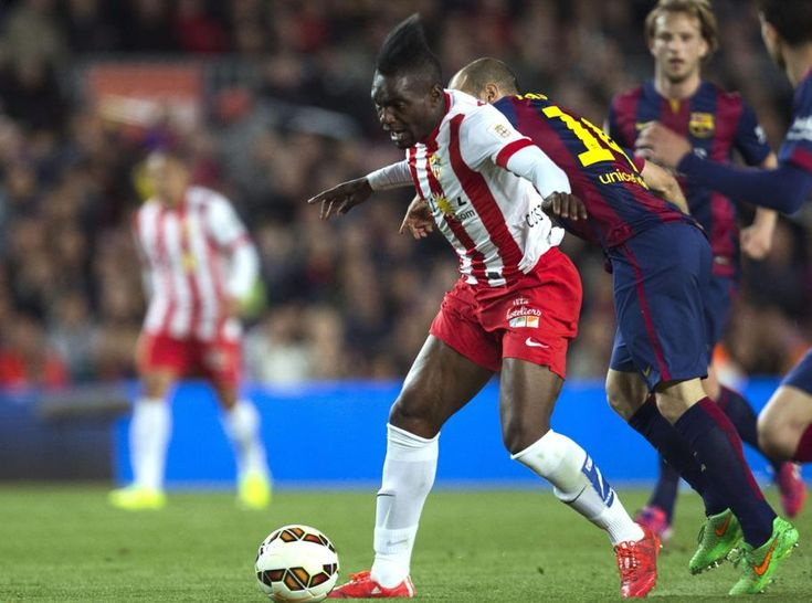 El delantero franco-congoleño del Almería, Thievy Bifouma, disputa el balón con el centrocampista argentino del FC Barcelona Javier Mascherano.