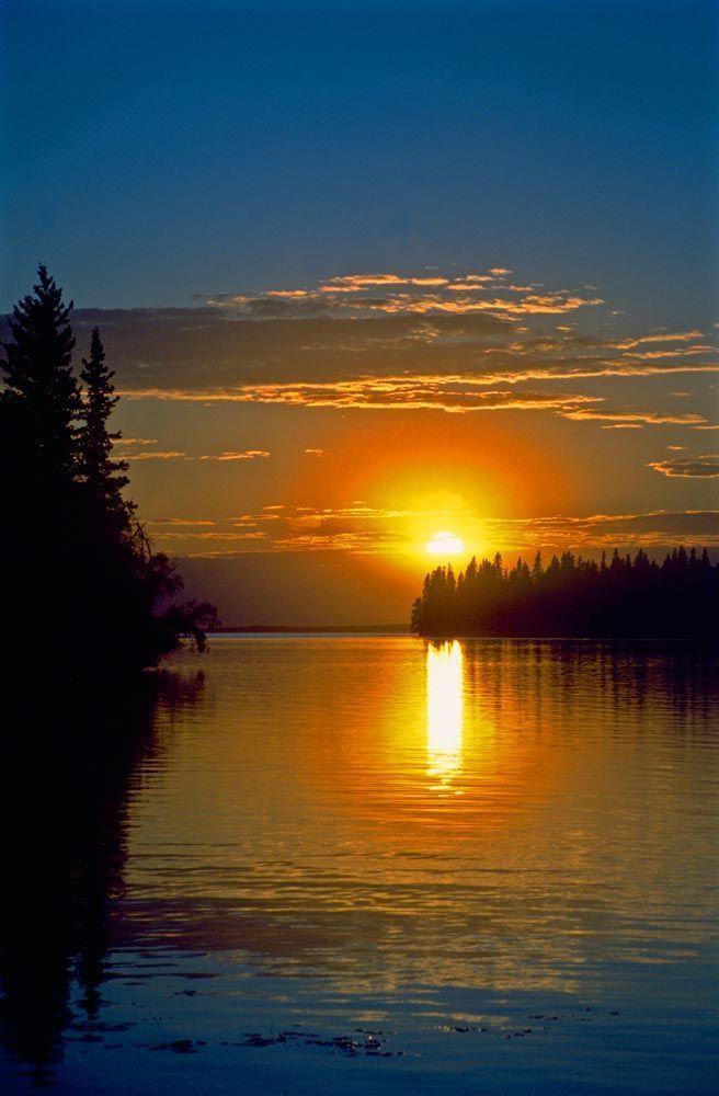 A warm golden-orange sunset over Clear Lake, Manitoba, Canada. #sunsets #Canada #travel