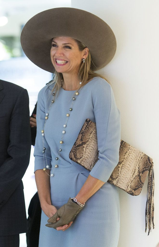 After getting caught in the rain in a beautiful gown and suede pumps, Queen Maxima has gotten original when it comes to protecting herself from a downpour with this oversized hat that rivals Pharell's.