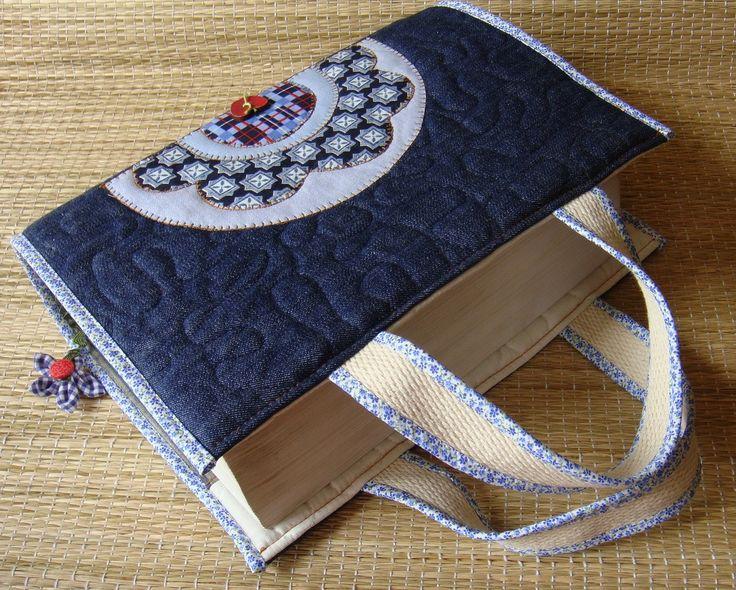 Capa para livro em patchwork confeccionada em jeans e algodão, estruturada com manta acrílica, com aplicações, marcador de páginas e alças para carregar Medidas aproximadas : A=27cm X L=43 cm (capa aberta) Cabe um livro de 8 cm de espessura. Serve nos livros : (Vade Mecum e Código de Processo Civil p/ as medidas acima). Para outras medidas de livro, é só entrar em contato. Obs- A padronagem dos tecidos poderá não ser a mesma da foto.