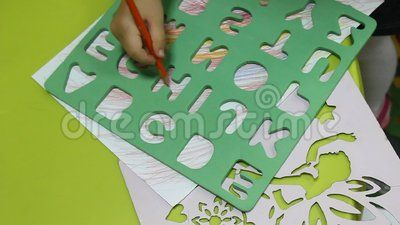 Preschool child during educational activities - drawing letters using template.