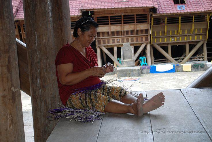 Seorang ibu menggunakan waktu luang dengan membuat tempat pinang. Lokasi: Desa Hilimondregeraya, Nias Selatan.