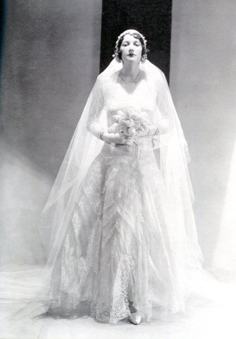 Chanel—long-sleeved and worn with gloves—and is made entirely of stiffened lace, worn by bride Betty Garst.1930