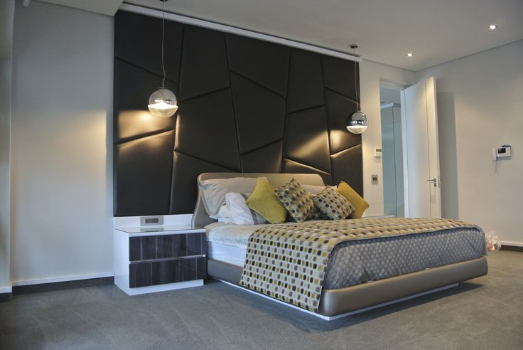 Bold, modern upholstered wall feature in this master bedroom