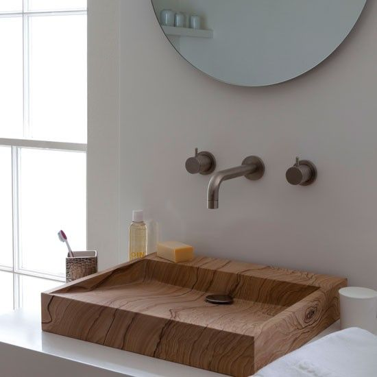 Wooden bathroom basin    This crisply-carved, wood-lookalike stone basin makes for a stunning feature in a simple, all-white scheme.    Basin and taps  Aston Matthews