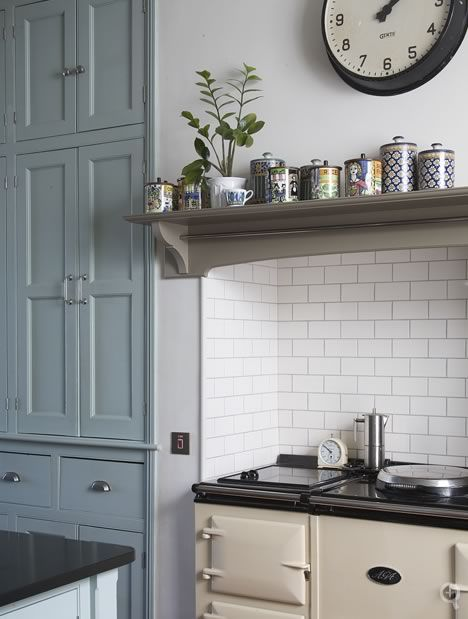 Kitchen cabinets hand-painted in Farrow  Ball's 'Green Blue' No.84, topped by a combination of honed African black granite and wide plank European oak worktops. And the aga stove