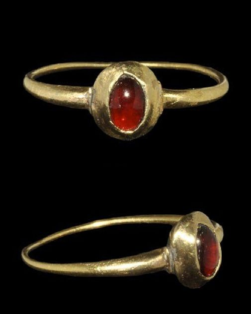 Gold ring with garnet cabochon, 14th C. AD . A delicate finger ring with fine expanding hoop, carinated shoulders and biconical bezel, elliptical in plan with inset cabochon garnet.