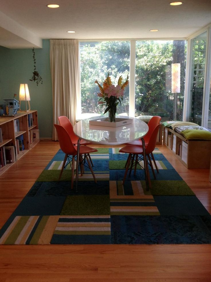 This colorful dining room features a mid-century modern white table and vibrant orange chairs with blue, green and yellow carpet tiles underneath. Hardwood floors are visible throughout the remaining space, while a bench seat with storage is located next to the window area, making it the perfect spot for enjoying natural light.