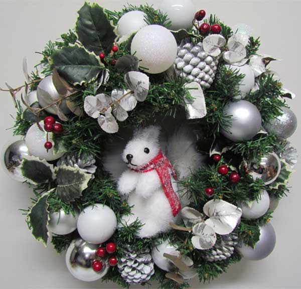 This wintry Christmas wreath features white and silver baubles with holly and silver pinecones. An adorable white squirrel peeks out from the centre.