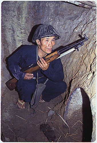 A Viet Cong soldier crouches in a bunker with an SKS rifle. 1968