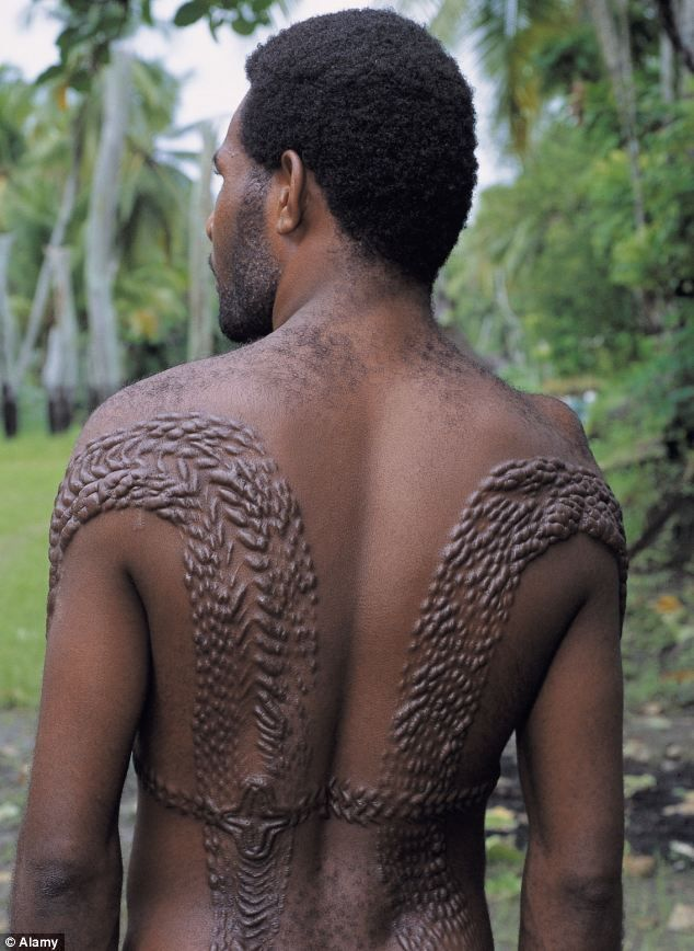 A man is pictured sporting skin decorations that pay tribute to crocodiles near Sepik Rive...
