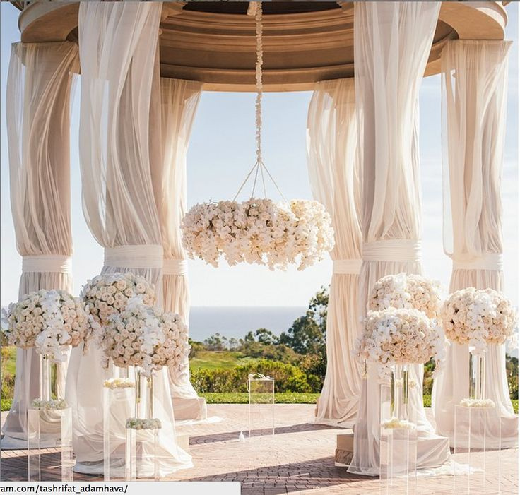| aboutdetailsdetails.com | ivory majestic flowing drapes, clear see through pedestals, ivory and white florals, hanging canopy of flowers, ceremony