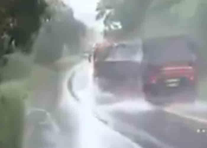 A driver traveling on wet roads rounds a corner to find stopped vehicles.