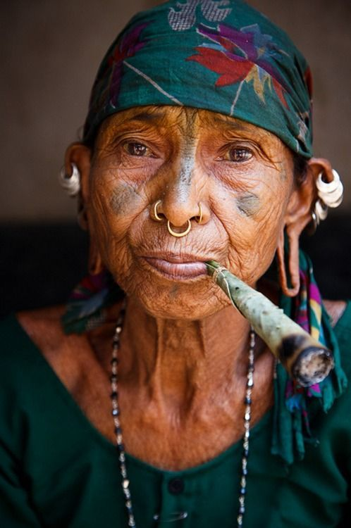 Portrait of a Lanjiya Soura tribal woman with traditional piercings and tattoos, smoking a large hand rolled cigarette