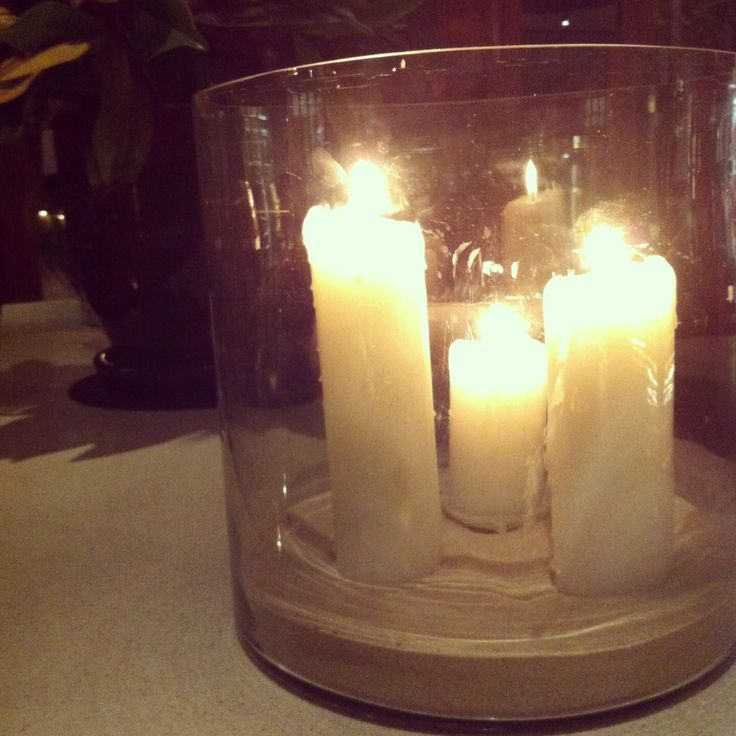 Pillar candles presented in large glass hurricane with sand