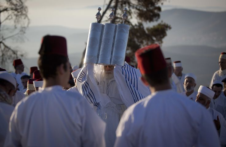 Members of the ancient Samaritan community hold up a Torah scroll during the holiday of Shavuot on Mount Gerizim near the West Bank town of Nablus.