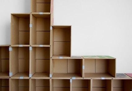 Back to the office supply and moving companies again! Face the backs of bottom row of boxes out so there aren't cubbies open on the lowest level if this will sit on the floor. Cardboard boxes and metal clips turned into a unique shelving display unit!