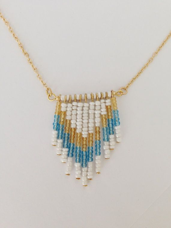White, blue and gold beaded chevron necklace. Gold finishes and gold chain. Finished with a spring ring clasp. Various necklace lengths are