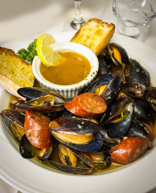 Prince Edward Island mussels steamed in a white wine sauce of tomatoes, garlic, red chili flakes and chorizo, a spicy sausage, for extra heat. Garlic toast points for dipping.