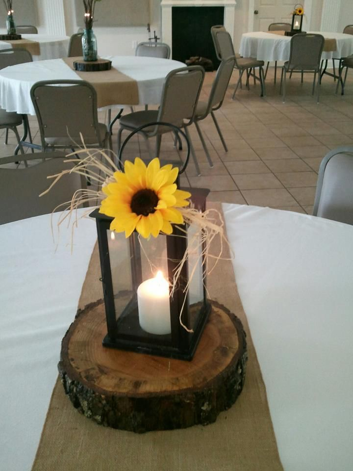 Lantern with candle and sunflower on top and a raffia bow.
