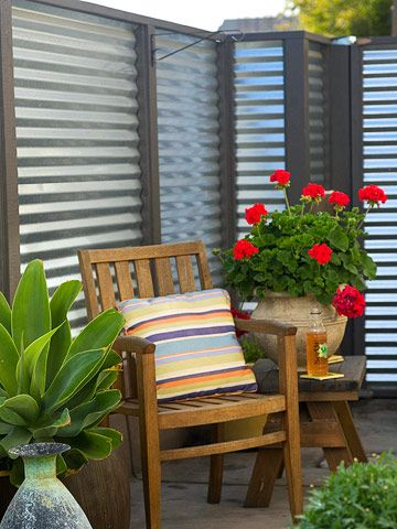 Embrace Heavy Metal...Give your garden a modern feel with a wall of inexpensive galvanized corrugated metal. Wood patio furniture and colorful geraniums soften the space. Horizontal stripes on a cushion mimic the texture of the metal sheeting.