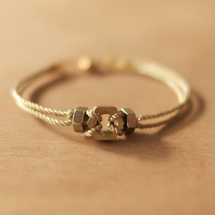 Handmade hex nut with gold metal thread bracelet. $6.00, via Etsy. Would love in silver and black..