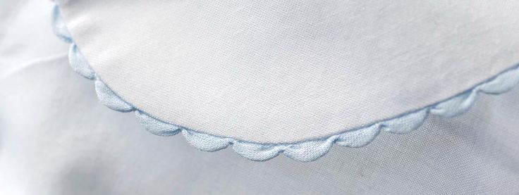 A sweet shell hem is a great finish for delicate baby clothes. Learn how to create this trim by machine.