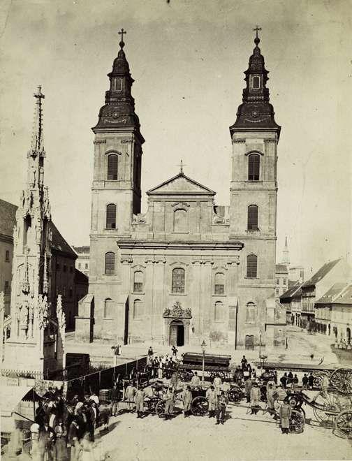 Március 15. (Eskü) tér, Belvárosi Nagyboldogasszony Főplébánia, balra a később elbontott Szentháromság-szobor. A \