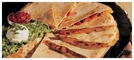 Chicken Quesadilla: Mezcla de queso, pollo grillado, tocino y pico de gallo entre dos tortillas de harina. Acompañados de lechuga, crema ácida, guacamole y salsa base picante. Foto referencial.