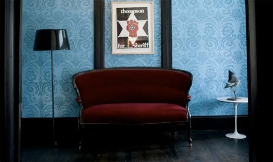 I like the blue on blue patterened wallpaper behind the dark burgundy couch.