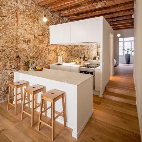 #reforma #cocina abierta en vivienda rehabilitada con península como separación y barra, paredes de piedra, suelo parqué.