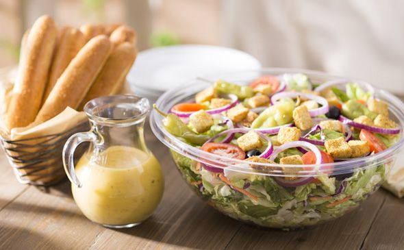 Olive Garden's salad is topped with olives, onions, pepperocinis, croutons, paremsan cheese, salad dressing, and tomatoes.