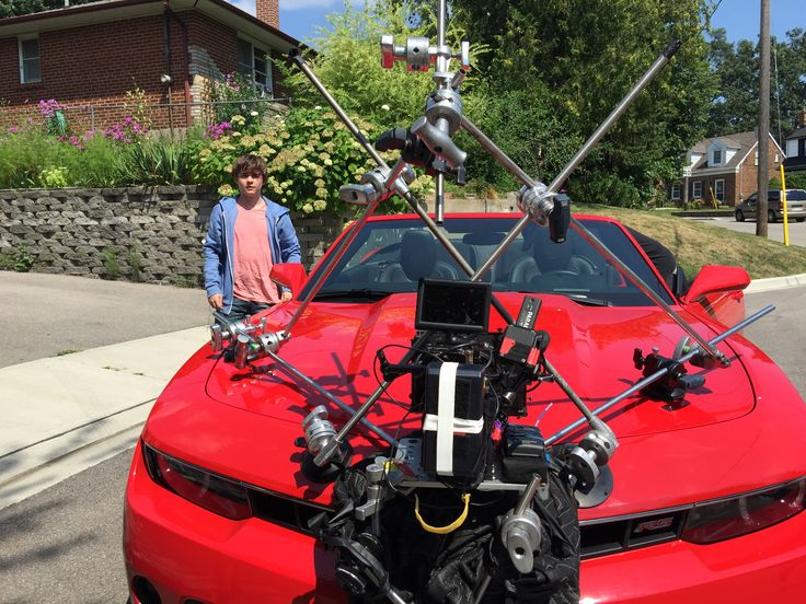 A Red Epic camera is attached to the very edge of the hood of Camarro convertible for a scene in Dumb Luck film. The star of the film Dylan Everett is seen beside the car. www.DumbLuckTheMovie.com #dumbluckthemovie #9LightEnt