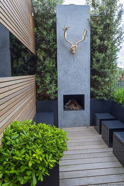 Tiny roof terrace | Outdoor fireplace on tiny urban balcony with timber screen, mirror, antlers, Pittosporum tobira in containers and stools | Charlotte Rowe Garden Design