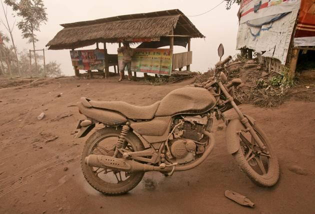 A motorcycle is covered in volcanic ash from an eruption of Mount Sinabung in Tiga Pancur, North Sumatra, Indonesia, Saturday, Jan. 4, 2014. The 2,600-meter (8,530-foot) volcano has sporadically erupted since September.