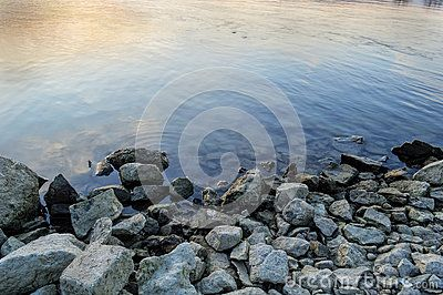 Pile of rocks on the shore on the banks of the Danube in the sunset or sunrise, Budapest, Hungary
