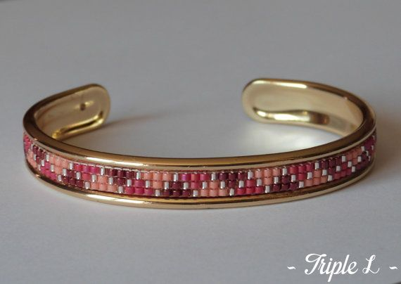 ~ DESCRIPTIF ~ Ce bracelet manchette LORÈNE est composé dun tissage fait main avec des perles de verre Miyuki et dune manchette en laiton à rebords dorés. Couleurs des perles : bordeaux - framboise - saumon - pêche brillant. Dimensions : 1 cm de large. ~ MATERIEL UTILISE ~ - Perles de verre japonaises Miyuki - Manchette en laiton doré à rebords dorés - origine : Europe  ~ ENVOI ~ Les bijoux sont envoyés en courrier suivi dans une enveloppe en papier bulle et soigneusement emballés…
