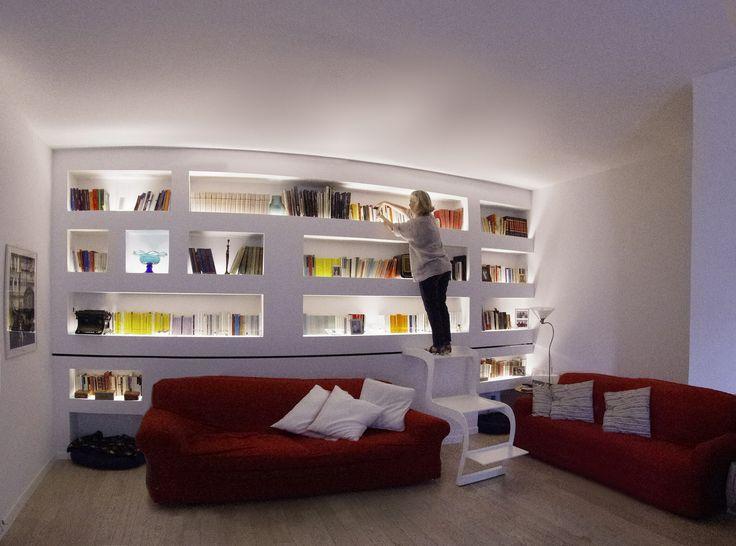"""Libreria """"MorSab"""" in cartongesso retro-illuminata con sistema di Carrello-Scala scorrevole frontalmente su tutta la parete / funge anche da tavolo di servizio .  Ha la caratteristica di scorrere passando sopra al divano, permettendo così l'uso della parte libreria, soprastante. Design / Realizzazione - Lauro Ghedini & Partners"""