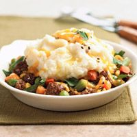 READY IN 20 MIN Potato Topped Beef Bowl  1  pound ground beef  1  16 ounce package frozen mixed vegetables  1  8 ounce package shredded cheddar cheese (2 cups)  1/4  cup snipped fresh Italian (flat-leaf) parsley  Salt and ground black pepper  2  cups instant mashed potato flakes  2  tablespoons butter, melted