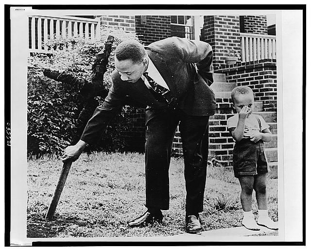 """Martin Luther King, Jr., pulling up a cross that was burned on the lawn of his home, as his son stands next to him.""""    Atlanta, Georgia - 1960."""