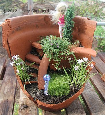 I LOVE it! Lesley Shepherd always comes up with clever ideas for miniatures, both indoors and out.       Doll standing in the top layer of a miniature garden planted in a broken flower pot.
